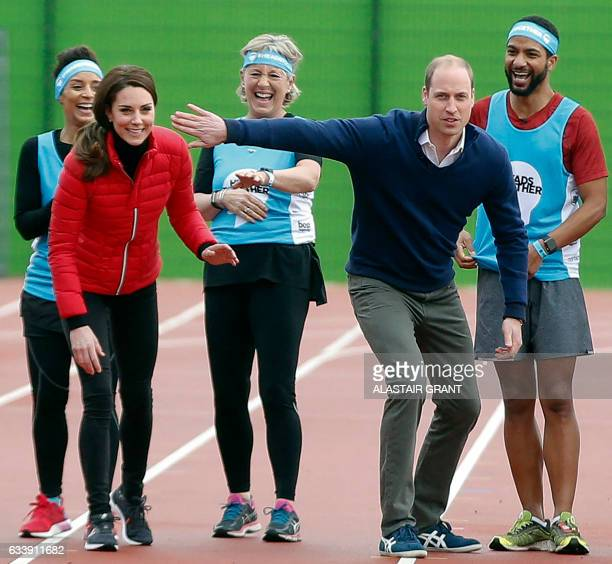 Britain's Catherine Duchess of Cambridge and Britain's Prince William Duke of Cambridge share a joke at the start of a relay race during a training...