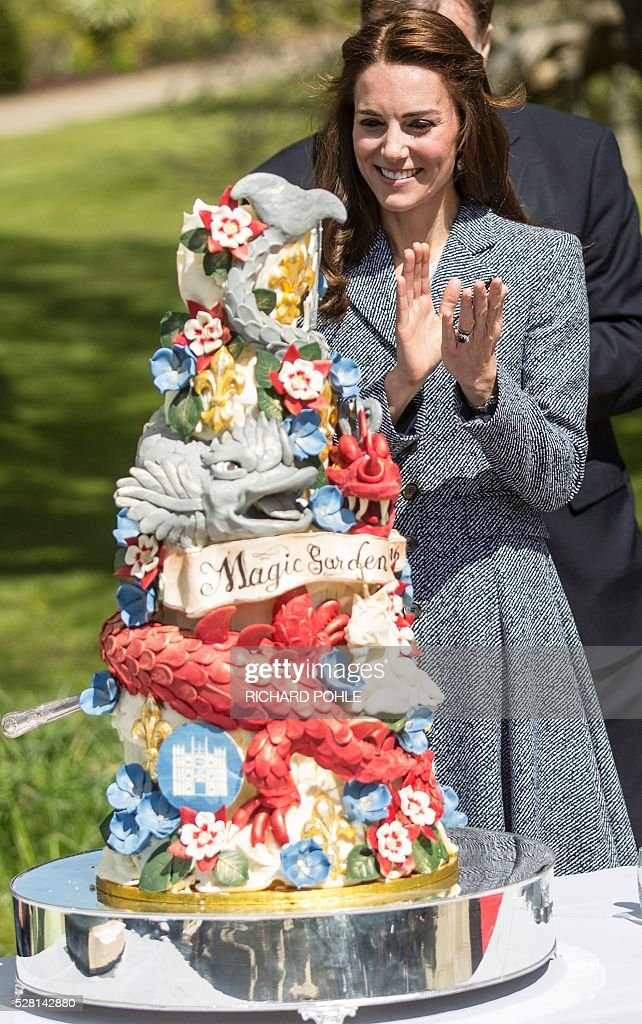 Britain's Catherine, Duchess of Cambridge, applauds beside an ornate cake decorated with dragons and magical creatures baked especially for the official opening of the 'Magic Garden' children's play area at Hampton Court Palace in south-west London on May 4, 2016. The Duchess's visit marked the official opening garden, which was designed by architect Robert Myers, and is said to draw inspiriation myts and legends of the Tudor Court. / AFP / POOL / RICHARD
