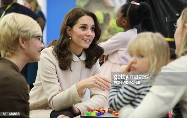 Britain's Catherine Duchess of Cambridge chats with mothers and children during her visit to the Hornsey Road Children's Centre in north London on...
