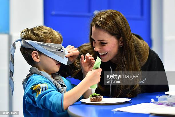 Britain's Catherine Duchess of Cambridge checks a boy's blindfold before helping him ice a cake as she promotes disability awareness while meeting...