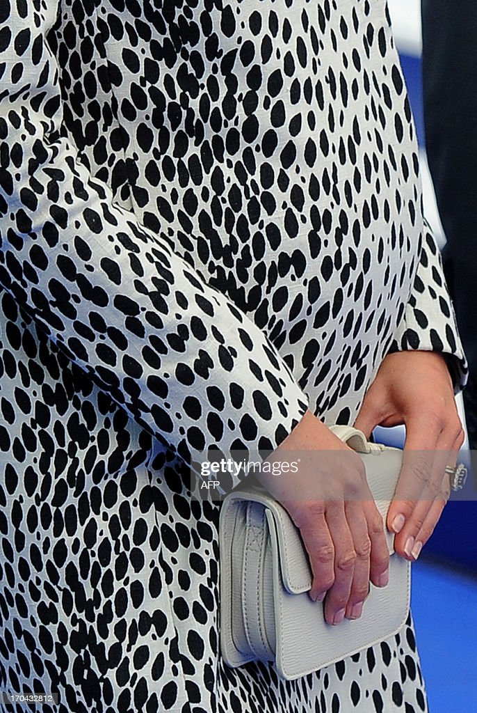 Britain's Catherine, Duchess of Cambridge clutches her handbag as she attends a ceremony to officially name Princess Cruises's new ship 'Royal Princess' in Southampton, southern England on June 13, 2013. The Duchess of Cambridge, as the ship's godmother, officially named the Royal Princess with a traditional blessing involving smashing a bottle over the ship's hull in what is expected to her final solo engagement before the birth of her and Prince William's child.