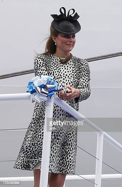 Britain's Catherine Duchess of Cambridge cuts the rope to release the bottle to smash on the hull during a ceremony to officially name the Princess...