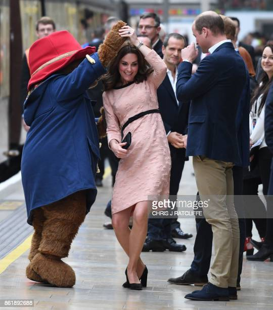 Britain's Catherine Duchess of Cambridge dances with a person in a Paddington Bear outfit by her husband Britain's Prince William Duke of Cambridge...