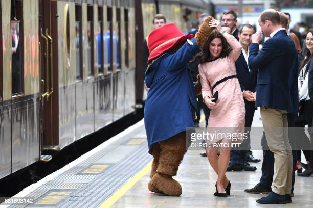 TOPSHOT Britain's Catherine Duchess of Cambridge dances with a person in a Paddington Bear outfit by her husband Britain's Prince William Duke of...