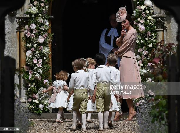 Britain's Catherine Duchess of Cambridge gestures as she walks with the bridesmaids and pageboys as they arrive for her sister Pippa Middleton's...