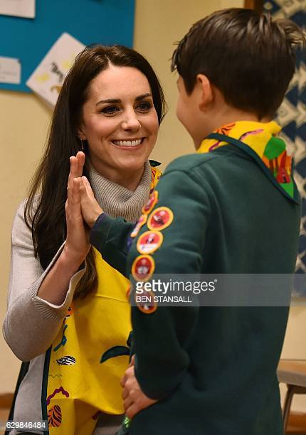 Britain's Catherine Duchess of Cambridge gives a highfive to a cub scout who showed her how to support a broken arm during a Cub Scout Pack meeting...