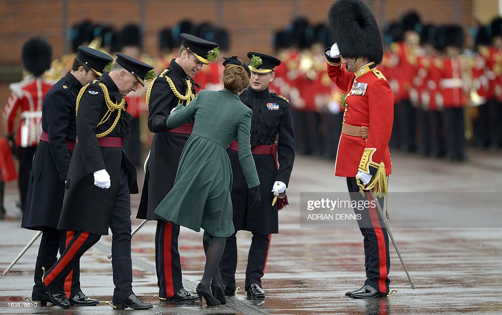 Britain's Catherine, Duchess of Cambridge, holds on to Britain's Prince William, Duke of Cambridge, as she tries to release her shoe that was stuck in the grate during St Patrick's Day parade in Mons Barracks in Aldershot on March 17, 2013. The Duke of Cambridge attended the parade as Colonel of the Regiment and Catherine presented the traditional sprigs of shamrocks to the Officers and Guardsmen of the Regiment.