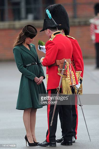Britain's Catherine Duchess of Cambridge is presented with a shamrock during a shamrock presentation ceremony for the Irish Guards on St Patrick's...