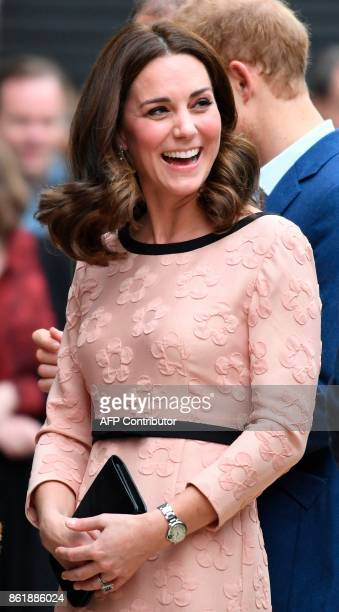 Britain's Catherine Duchess of Cambridge laughs as she arrives to attend a charities forum event at Paddington train station in London on October 16...