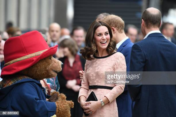 Britain's Catherine Duchess of Cambridge laughs as she meets a person in a Paddington Bear outfit along with her husband Britain's Prince William...