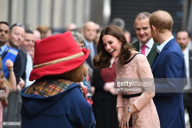 Britain's Catherine Duchess of Cambridge laughs as she meets a person in a Paddington Bear outfit along with Britain's Prince Harry as they attend a...