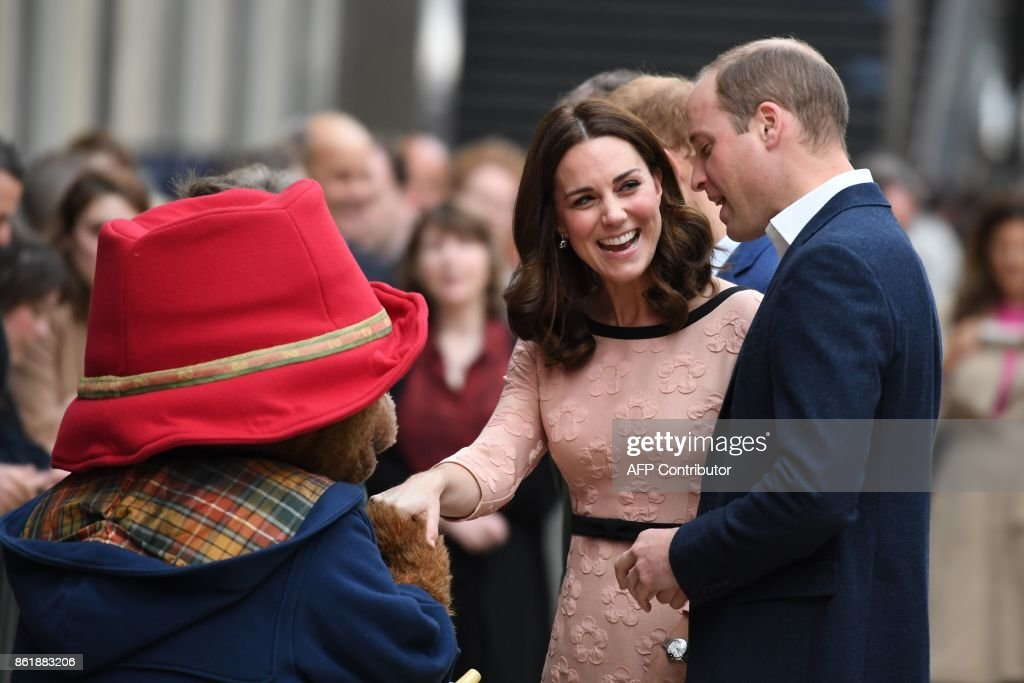 Britain's Catherine, Duchess of Cambridge, (C) laughs as she shakes hands with a person in a Paddington Bear outfit along with her husband Britain's Prince William, Duke of Cambridge, (R) as they attend a charities forum event at Paddington train station in London on October 16, 2017. The Duke and Duchess of Cambridge and Prince Harry joined children from the charities they support on board Belmond British Pullman train at Paddington Station. The event was hosted by STUDIOCANAL, with support from BAFTA through its BAFTA Kids programme, and before embarking Their Royal Highnesses met the cast and crew from the forthcoming film Paddington 2. / AFP PHOTO / Chris J Ratcliffe