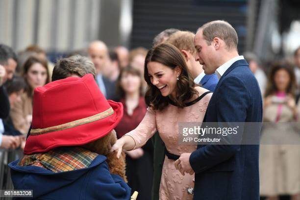 Britain's Catherine Duchess of Cambridge laughs as she shakes hands with a person in a Paddington Bear outfit along with her husband Britain's Prince...