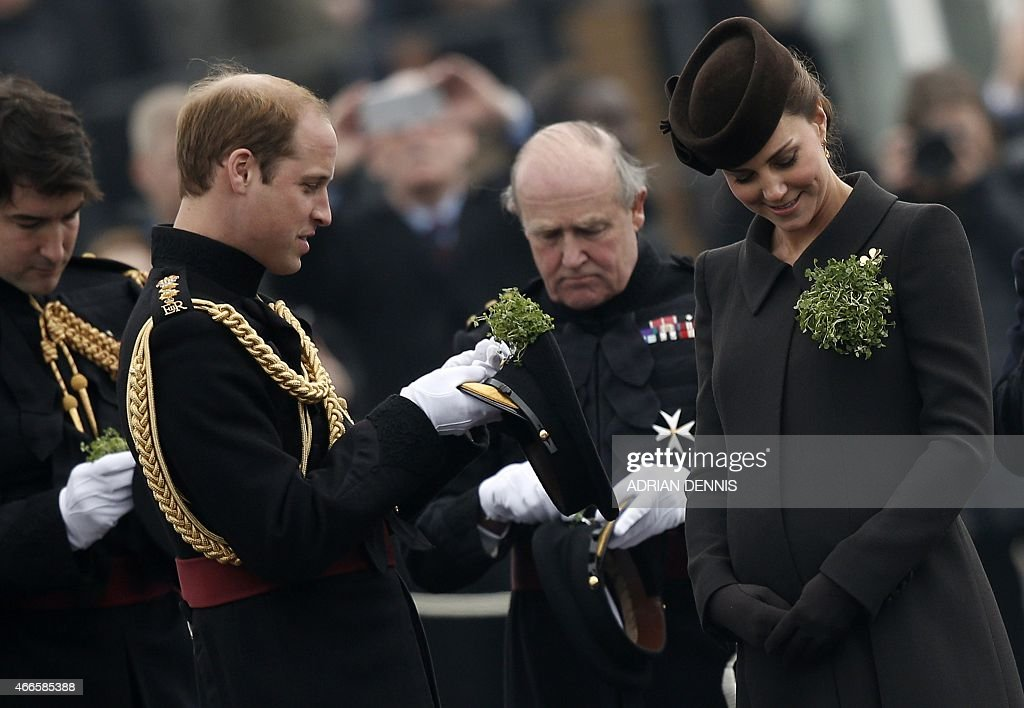 Britain's Catherine Duchess of Cambridge looks at her shamrock as her husband Britain's Prince William Duke of Cambridge attaches a shamrock to his...