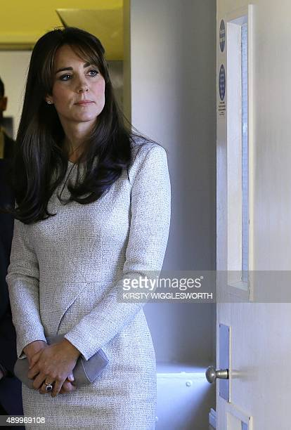 Britain's Catherine Duchess of Cambridge looks through a window durin a visit to the women's HM Prison Send near Woking Surrey on September 25 2015...