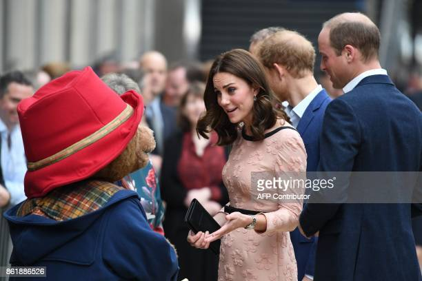 Britain's Catherine Duchess of Cambridge meets a person in a Paddington Bear outfit along with Britain's Prince William Duke of Cambridge as they...