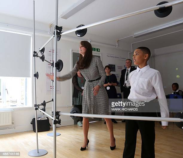Britain's Catherine Duchess of Cambridge plays a coordination game with Kaionel who took her around his class during her visit to the Anna Freud...