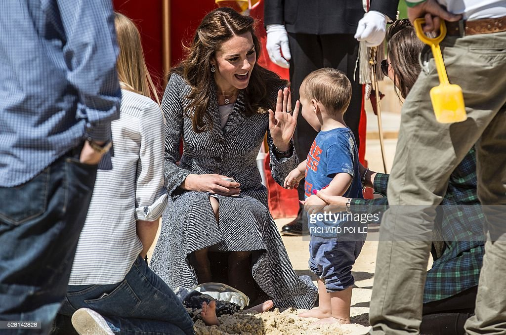 Britain's Catherine, Duchess of Cambridge, plays with a youngster in a sand pit as she visits the newly opened 'Magic Garden' children's play area at Hampton Court Palace in south-west London on May 4, 2016. The Duchess's visit marked the official opening garden, which was designed by architect Robert Myers, and is said to draw inspiriation myts and legends of the Tudor Court. / AFP / POOL / RICHARD