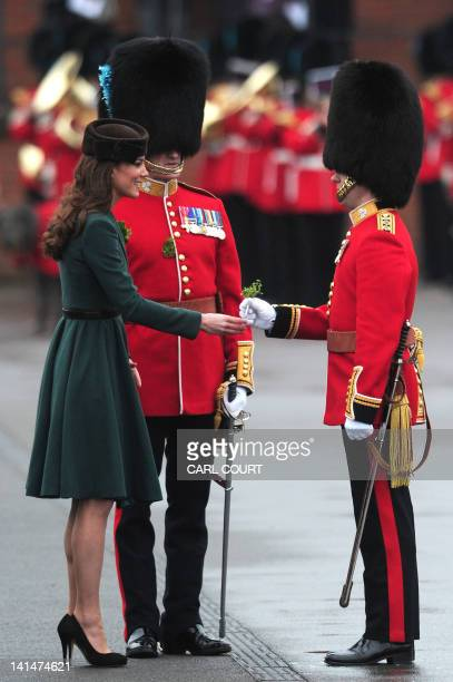 Britain's Catherine Duchess of Cambridge presents a basket of shamrock sprigs to the Irish Guards regiment during a shamrock presntation ceremony on...