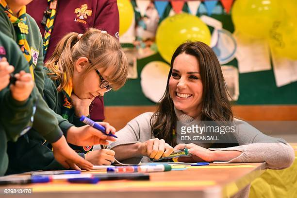 Britain's Catherine Duchess of Cambridge reacts as she talks with cubs during a Cub Scout Pack meeting with cubs from the Kings Lynn District in...