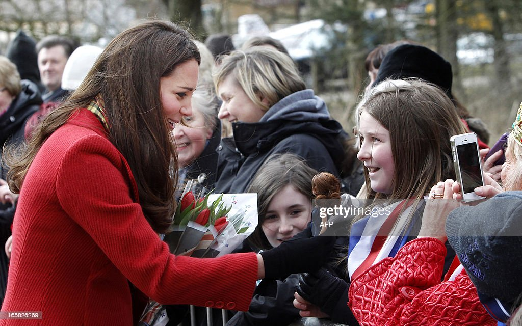 Britain's Catherine, Duchess of Cambridge, reacts as young Dayna Miller shows her a doll made to look after the Duchess during the formr's visit to Dumfries House in Ayrshire, Scotland, on April 5, 2013. The Duke and Duchess of Cambridge braved the bitter cold to attend with Prince of Wales the official opening of the Tamar Manoukin Outdoor Centre. AFP PHOTO/POOL/DANNY LAWSON