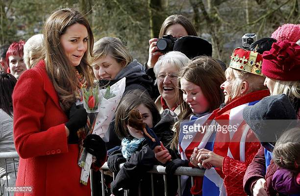 Britain's Catherine Duchess of Cambridge reacts as young Dayna Miller shows her a doll made to look after the Duchess during the formr's visit to...
