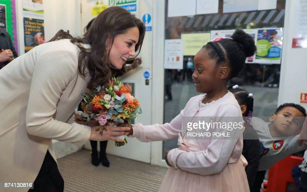 Britain's Catherine Duchess of Cambridge receives a bunch of flowers from six year old Nevaeh during her visit to the Hornsey Road Children's Centre...