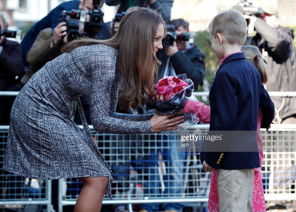 Britain's Catherine, Duchess of Cambridge receives flowers from Hugh and Serena Woodford after a visit to Hope House charity in south London on February 19, 2013. The Duchess visited Hope House, an all-female rehabilitation centre which is is one of the projects run by her patronage, Action on Addiction.