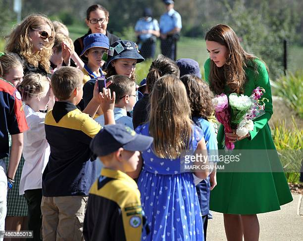 Britain's Catherine Duchess of Cambridge receives flowers from children while visiting the National Arboretum in Canberra on April 24 2014 Britain's...