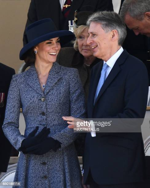 Britain's Catherine Duchess of Cambridge smiles a she talks to British Chancellor of the Exchequer Philip Hammond as they attend a Service of...