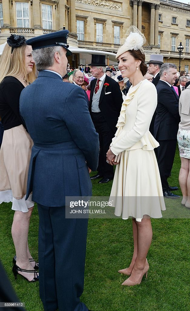 Britain's Catherine, Duchess of Cambridge (R), smiles as she greets guests attending a garden party at Buckingham Palace in London on May 24, 2016. / AFP / POOL / John Stillwell