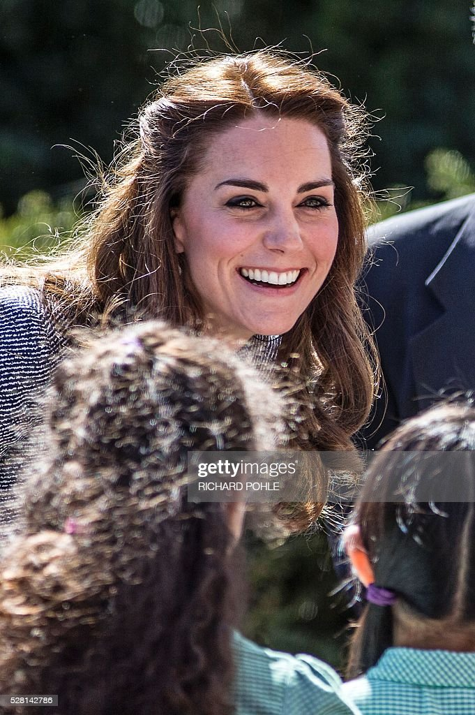 Britain's Catherine, Duchess of Cambridge, smiles as she talks to local school children, as they play in the newly opened 'Magic Garden' children's play area at Hampton Court Palace in south-west London on May 4, 2016. The Duchess's visit marked the official opening garden, which was designed by architect Robert Myers, and is said to draw inspiriation myts and legends of the Tudor Court. / AFP / POOL / RICHARD