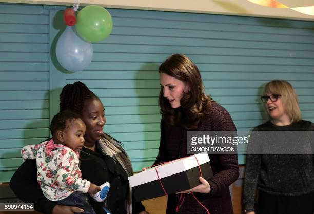 Britain's Catherine Duchess of Cambridge speaks to children during a visit to the Rugby Portobello Trust's Christmas party which included children...