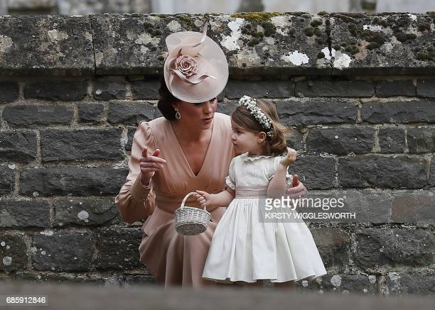 TOPSHOT Britain's Catherine Duchess of Cambridge speaks to her daughter Britain's princess Charlotte a bridesmaid following the wedding of her sister...