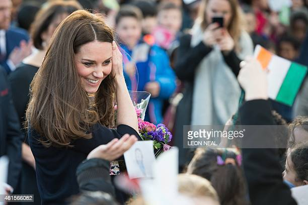 Britain's Catherine Duchess of Cambridge speaks with children as she leaves after an official visit to Barlby primary school in central London on...
