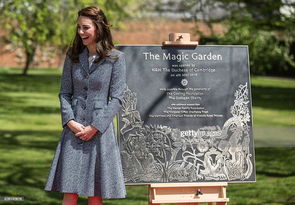 Britain's Catherine, Duchess of Cambridge, stands beside the plaque she unveiled at the official opening of the 'Magic Garden' children's play area at Hampton Court Palace in south-west London on May 4, 2016. The Duchess's visit marked the official opening garden, which was designed by architect Robert Myers, and is said to draw inspiriation myts and legends of the Tudor Court. / AFP / POOL / RICHARD