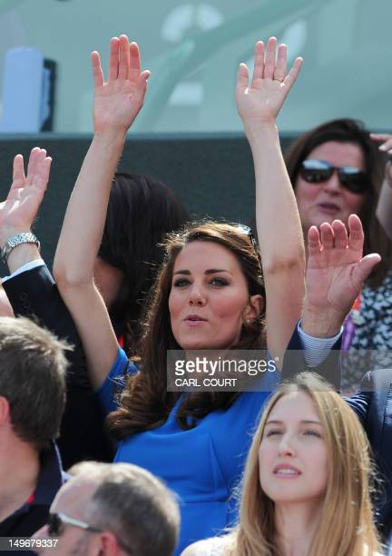 Britain's Catherine Duchess of Cambridge takes part in a Mexican wave as Britain's Andy Murray plays Spain's Nicolas Almagro in their London 2012...
