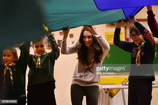 Britain's Catherine Duchess of Cambridge takes part in a parachute game during a Cub Scout Pack meeting with cubs from the Kings Lynn District in...