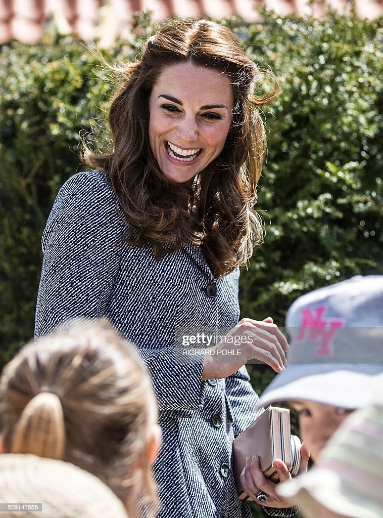 Britain's Catherine, Duchess of Cambridge, talks to local school children as they play in the newly opened 'Magic Garden' children's play area at Hampton Court Palace in south-west London on May 4, 2016. The Duchess's visit marked the official opening garden, which was designed by architect Robert Myers, and is said to draw inspiriation myts and legends of the Tudor Court. / AFP / POOL / RICHARD