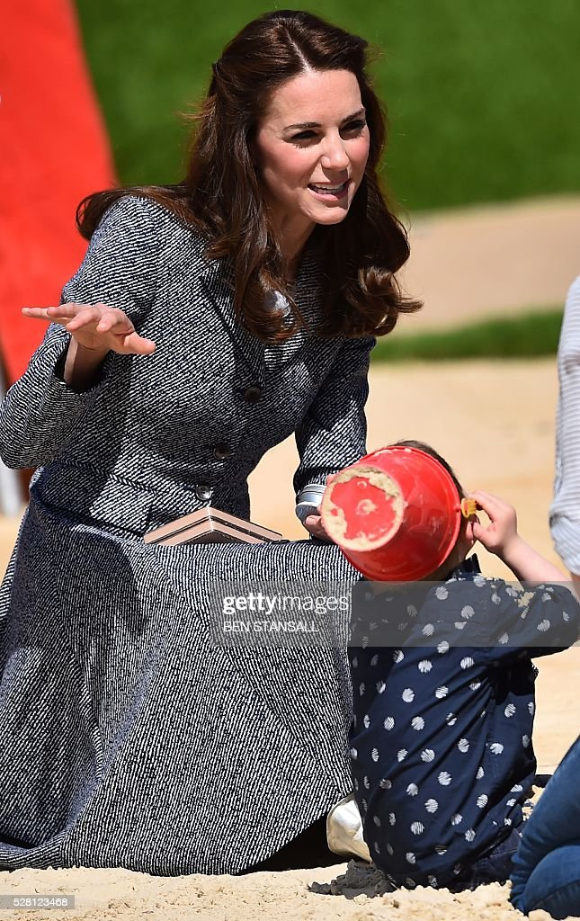 Britain's Catherine, Duchess of Cambridge, tours the 'Magic Garden' children's play area at Hampton Court Palace in south-west London on May 4, 2016. The Duchess's visit marked the official opening garden, which was designed by architect Robert Myers, and is said to draw inspiriation myts and legends of the Tudor Court. / AFP / BEN