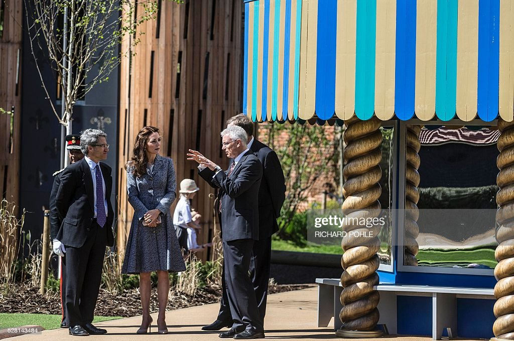 Britain's Catherine, Duchess of Cambridge (2nd L), tours the newly opened 'Magic Garden' children's play area at Hampton Court Palace in south-west London on May 4, 2016. The Duchess's visit marked the official opening garden, which was designed by architect Robert Myers, and is said to draw inspiriation myts and legends of the Tudor Court. / AFP / POOL / RICHARD