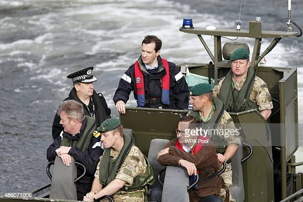 Britain's Chancellor of the Exchequer George Osborne arrives by boat during a visit to the Royal Navy's submarine base at Faslane on August 31 2015...