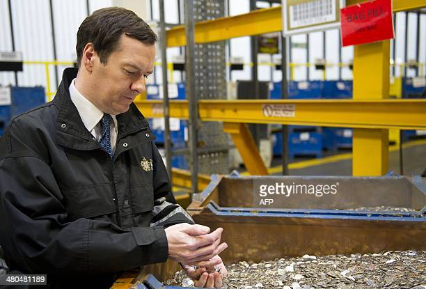 Britain's Chancellor of the Exchequer George Osborne holds freshly minted coins during a visit to the Royal Mint in Llantrisant Wales on March 25...