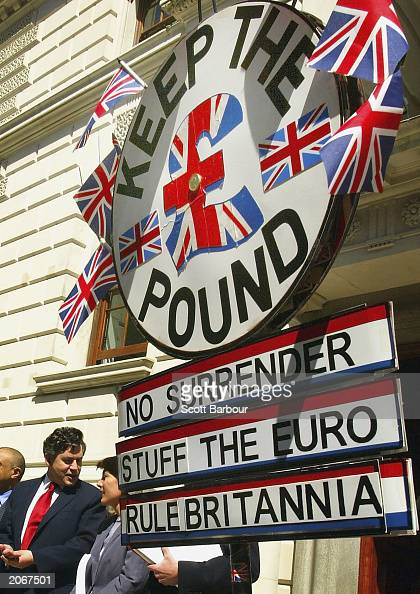 Britain's Chancellor of the Exchequer Gordon Brown leaves the Treasury building as an antieuro protester holds his placard aloft June 9 2003 in...