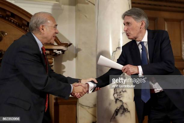 Britain's Chancellor of the Exchequer Philip Hammond shakes hands with the SecretaryGeneral of the Organisation for Economic Cooperation and...