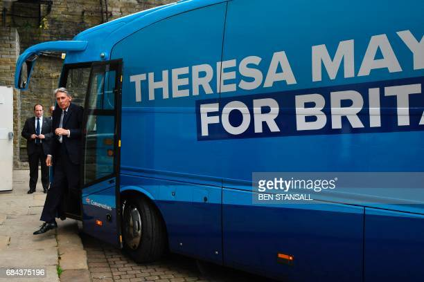 Britain's Chancellor of the Exchequer Philip Hammond steps off the Conservative Party 'Battle Bus' arriving at an event to launch the Party's general...