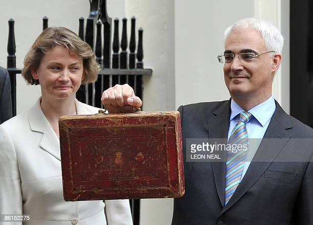 Britain's Chief Secretary to the Treasury Yvette Cooper watches as Finance Minister Alistair Darling poses for pictures with a briefcase containing...