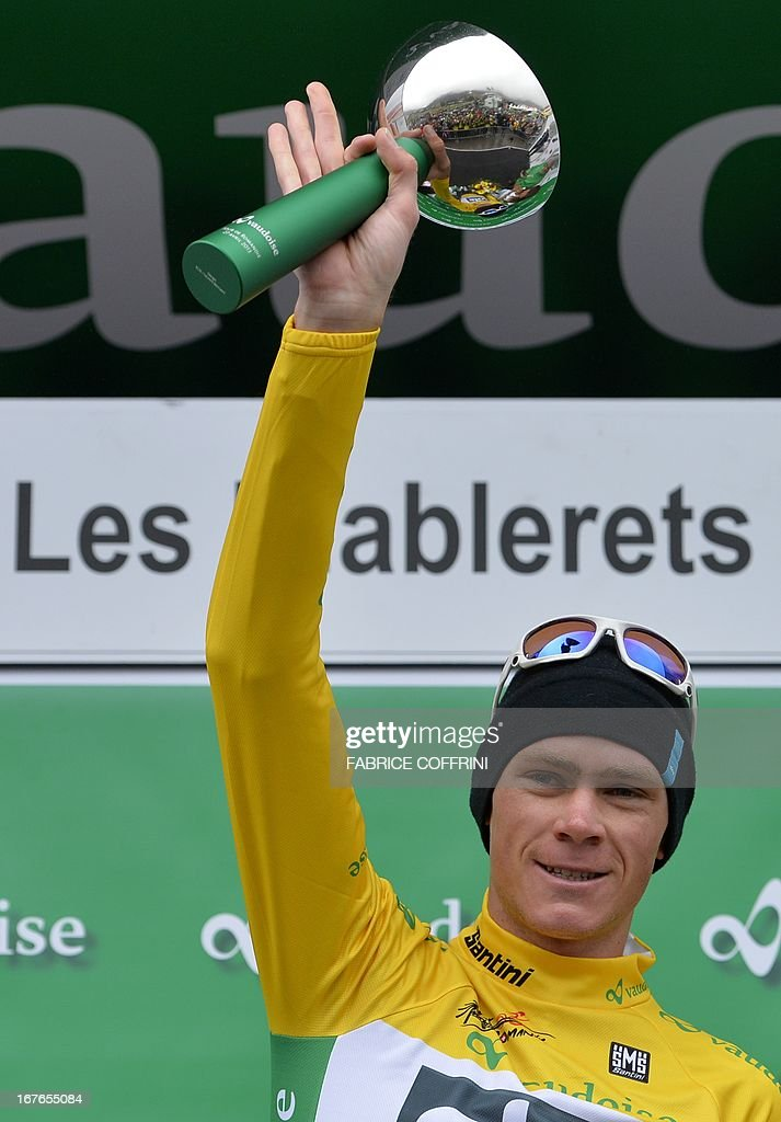 Britain's Christopher Froome celebrates on the podium after wearing the overall leader yellow jacket on the podium of the fourth stage of the Tour de Romandie cycling race on April 27, 2013 in Les Diablerets.