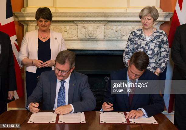 Britain's Conservative party leader and Prime Minister Theresa May stands Democratic Unionist Party leader Arlene Foster as DUP MP Jeffrey Donaldson...
