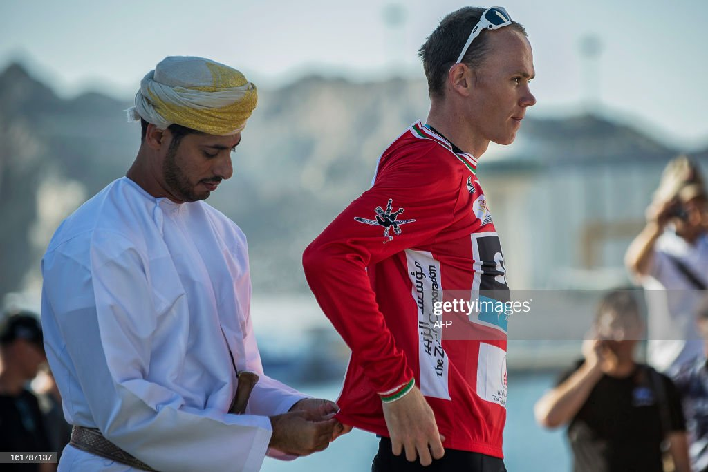 Britain's cyclist of Sky Procycling Team Christopher Froome (R) receives the leader's red jersey at the end of the sixth and last stage of the cycling Tour of Oman, on February 16, 2013, in the Omani capital Muscat. The final stage was a 144km ride from Hawit Nagam park in the south of the emirate to Muscat along the Matrah corniche.